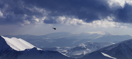 Wall Mural - Off-piste slope for heliskiing and helicopter in evening mountains