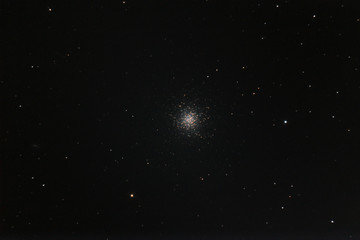 Globular cluster Messier 13 taken by telescope in the dark space with many stars as background.