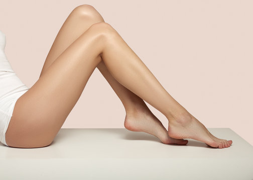 legs of a woman on a pink background. hair removal concept. Smooth and slim
