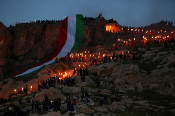 Iraqi Kurdish people carry fire torches up a mountain, as they celebrate Nowruz Day, a festival marking the first day of spring and the new year, in the town of Akra