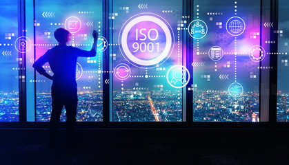 ISO 9001 with man writing on large windows high above a sprawling city at night