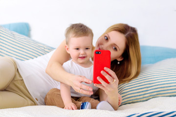 Mother takes pictures of her boy in bed with smartphone. Boy takes selfie with cell phone camera