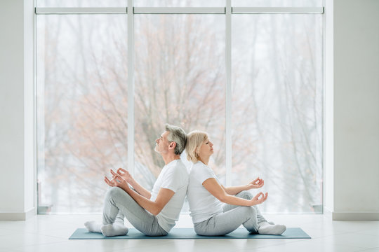 Beautiful senior couple practicing yoga together in the white gym with panoramic windows. Health and sport concept.Harmony and calm.