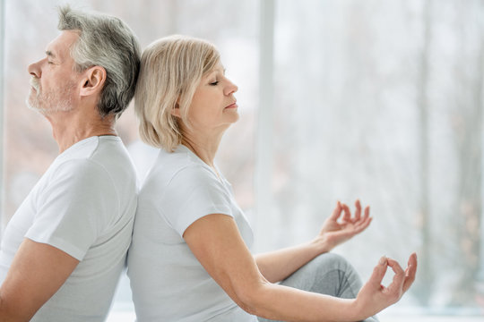 Health and sport concept.Harmony and calm. Cropped picture of senior couple doing yoga together in the white gym.