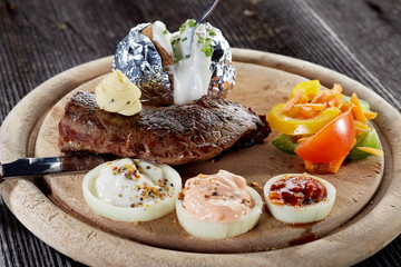 Rustic beef steak with oven potato and herb butter