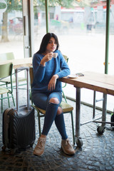 Beautiful young woman sitting while drinking a coffee in a cafe