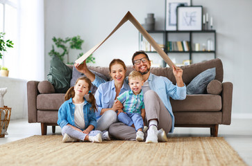 concept of housing and relocation. happy family mother father and kids with roof at home . Wall mural