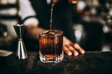 A close up shot of a bartender pouring whiskey. Classic old fashioned cocktail served with a cube of ice. Concept of bourbon whisky, spirits and alcohol.