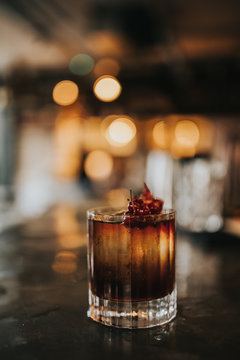 A close up shot of classic Old Fashioned cocktail served with a cube of ice and garnished with cranberries. Concept of bourbon whisky, spirits and alcohol.