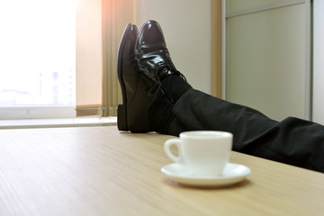 Male legs lying on table in office at work