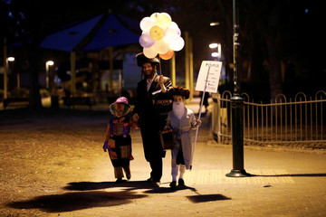 An Ultra Orthodox Jewish family dressed in costumes walk during the Jewish holiday of Purim, Israel