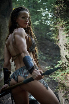 Beautiful amazon girl in metal mail with a spear in the forest.