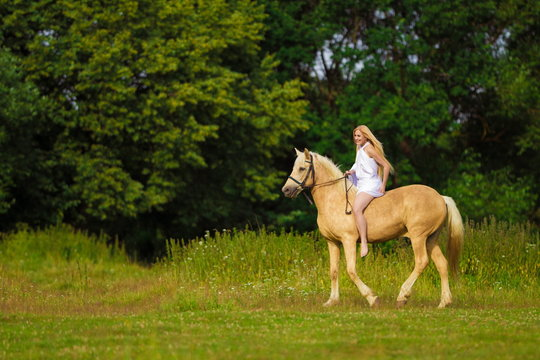 Young rider woman blonde with long hair in a white dress with a train posing and jumping on a palamino horse against a field and forest background
