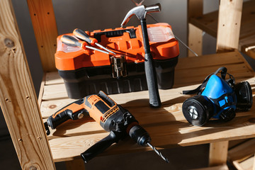 Set of various different tools in sunlight. Plastic tools kit, hammer, drill, gloves. Construction and home renovation concept with copy space