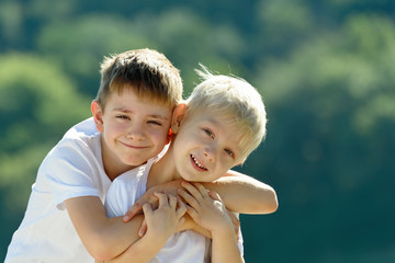 Two little boys are hugging outdoors. Concept of friendship and fraternity Wall mural