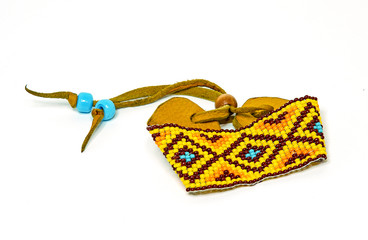 Beaded Bracelet in Native American design with yellow, burgundy, orange and turquoise beads on leather strap.
