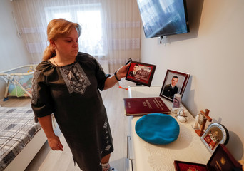 Paselsky, mother of Nazar Paselsky, who was killed in the Luhansk region, shows his photos, diploma and bravery award in her flat in Lviv