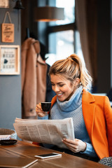 Happy businesswoman drinking coffee and reading newspaper in cafeteria.