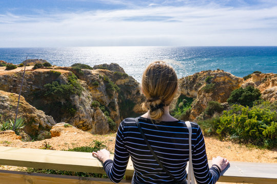 Young blonde haired woman looks out over beautiful ocean scene in Portugal