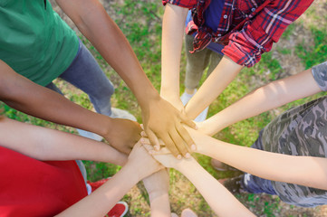 Group of volunteers putting hands together outdoors, top view