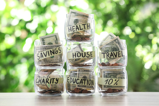 Glass jars with money for different needs on table against blurred background
