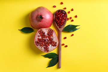 Flat lay composition with ripe pomegranates and wooden spoon on color background