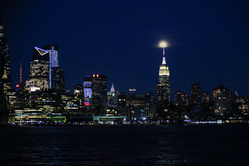 "The skyline of New York City is seen as the ""Worm moon"", the last Supermoon sighting of 2019,  rises over the Empire State Building, as seen from Hoboken in New Jersey"