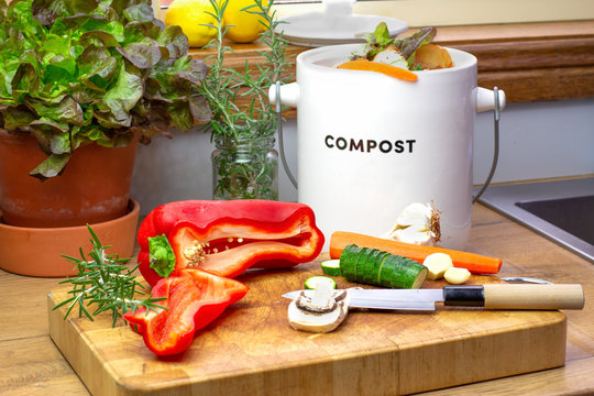 recycle food waste kitchen compost collecting container with chopped vegetables with knife on chopping board, sustainable living concept