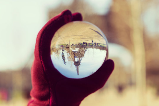 Female hand holding lensball with refraction of the Eiffel Tower in France, Paris