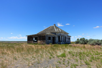 An abandoned house in rural Eastern Oregon on a summer day