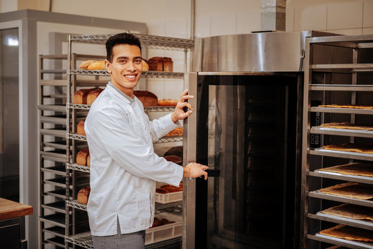 Pleasant baker standing near big oven in the kitchen