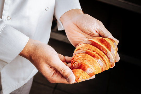 Yummy French croissant in hands of professional baker