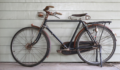 Old Ancient bicycle on the background of a gray wooden wall.