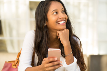 Young woman talking and texting on her mobile phone.