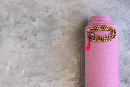 Rolled yoga mat and classic mala beads , essential things for yoga practice y meditation..Copy space.