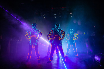 laser show performance, dancers in suits with LED lamp Wall mural
