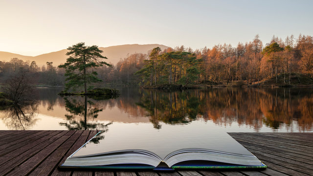 Beautiful landscape image of Tarn Hows in Lake District during beautiful Autumn Fall evening sunset with vibrant colours and still waters coming out of pages in magical story book