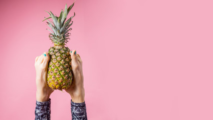 Sport and healthy eating lifestyle. Young woman doing yoga headstand and holding pineapple with her feet