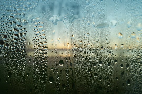 Raining water drops on a wet window closeup image. Condensed moisture on a glass surface in the morning. Sunrise on the background. Hope, faith and a fresh start in concept.