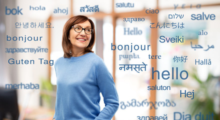 vision and old people concept - smiling senior woman in glasses over greeting words in different...