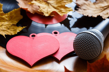 Song for lovers. Nostalgic songs, fallen autumn leaves and melancholy. Concept with vinyl records, microphone and hearts.