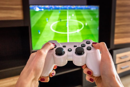 White gaming joystick, gamepad, standard controller is aimed at the TV, fifa football game ps4, xbox