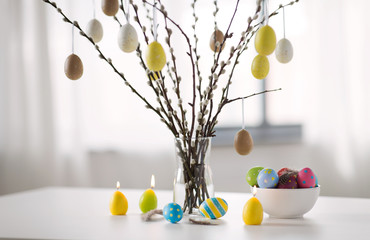 holidays and object concept - pussy willow branches decorated by easter eggs in vase and candles on table