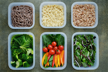 Vegan meal prep lunch box containers with quinoa, brown rice, buckwheat noodles, spinach, tomato, pepper, broccoli, savoy cabbage, lettuce, onions