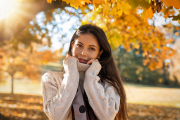 Young, attractive woman in the park during autumn time with orange leaves on the trees and golden sunshine