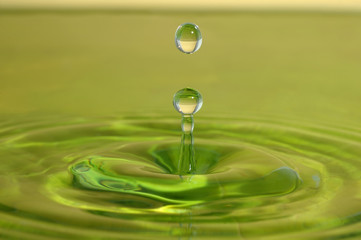 Green drop fall on water surface