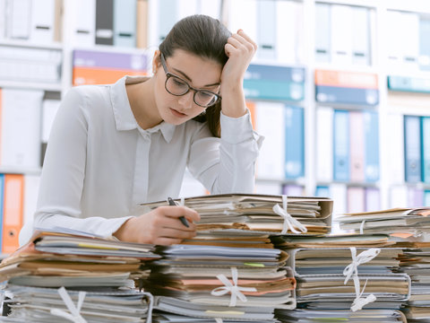 Sad young office worker overloaded with work