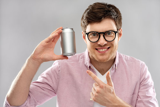 drinks and people concept - happy young man in glasses holding tin can with soda over grey background