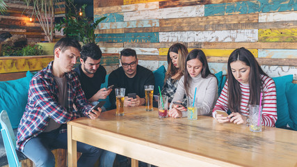 Group of friends at restaurant ignoring each other in favour of mobile phone - Young people addicted by mobile phone on social network,  Connected millennials interacting with smartphones online
