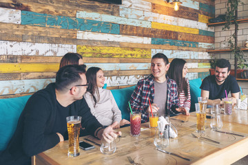 Happy group of best friends having fun drinking beer while waiting food order at restaurant – young people enjoying time together laughing at jokes and celebrate friendship